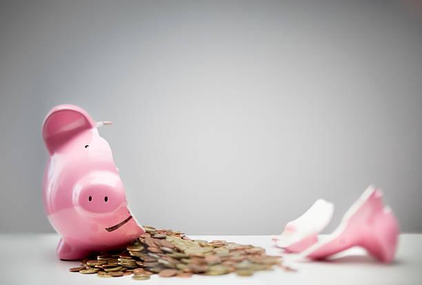 Money coming out of a broken piggy bank